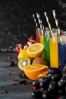 A set of cool fresh squeezed juices or cocktails in a glasses made from orange, kiwi, lemon, grapes, pomegranates