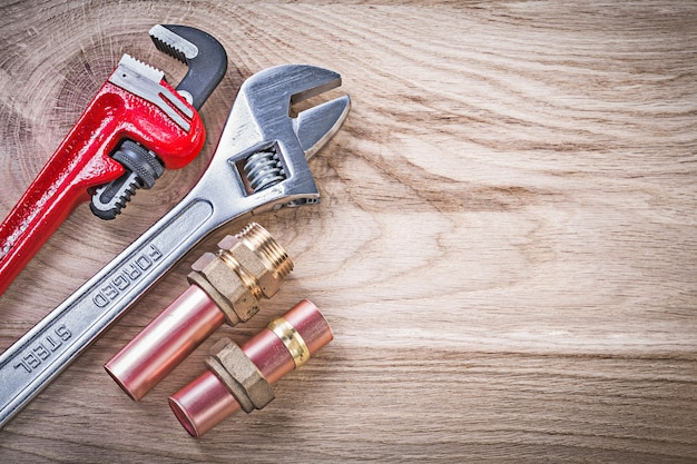 Set of copper water pipe wrench hose nipples adjustable spanner on wooden board plumbing concept
