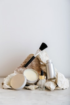 Set of cosmetic products in aluminum packaging. zero waste cosmetic products for skincare on pastel colors stone pedestal layout. minimal aesthetic.