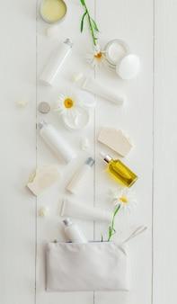 花、化粧品バッグと木製のテーブルに白いパッケージで化粧品を設定します。ビューティースキンケアヘアトリートメントコスメティックセラムオイルモイスチャライザースキンクリームボディバターソープローションシャンプー。フラットレイ
