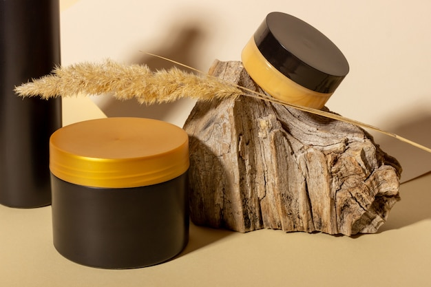 A set of cosmetic products next to a log and hard shadows on a beige background. natural organic cosmetics