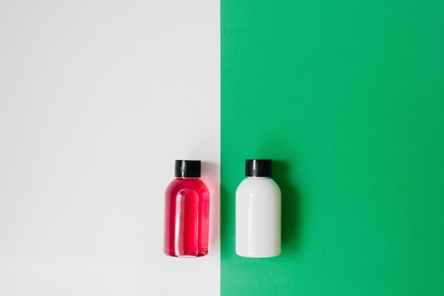 Set of cosmetic products for shower or bath, white and pink bottles on white and green background. copy space