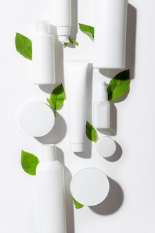 A set of cosmetic products in white tubes and with green leaves with empty space for labeling. natural cosmetics for face and body skin care. moisturizing cream, purifying mask.