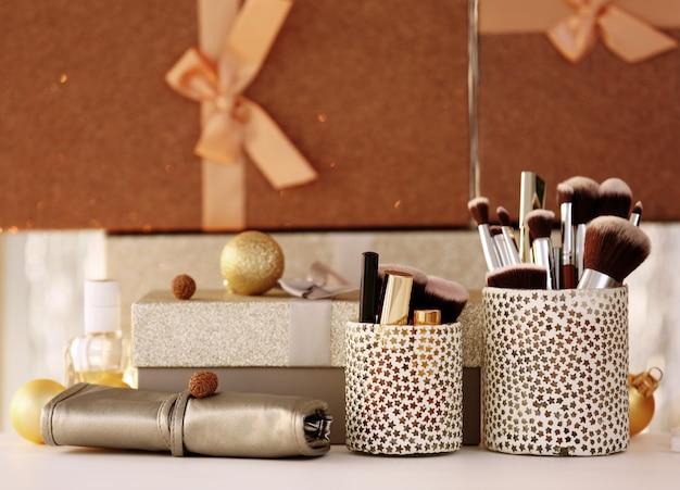 Set of cosmetics and box with present on white table against blurred surface