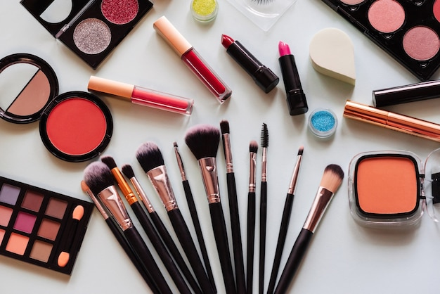 Set of cosmetics and brushes on a light background. view top