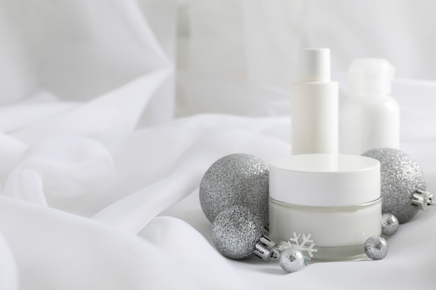Набор косметики, баночка зимнего крема для кожи на белой ткани, крупным планом. вид сверху
