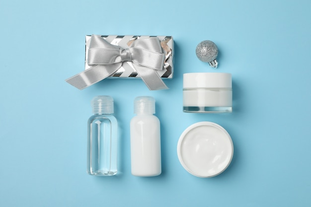 Set cosmetics, jar of winter cream for skin, gift box on blue background, space for text. top view