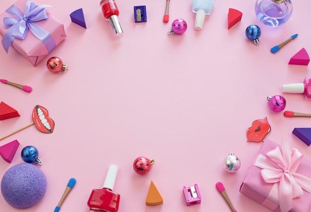 Set   cosmetics nail polish lipstick sponge sharpener box gift ribbon satin bow background pink
