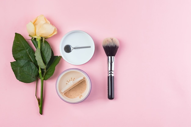 Set of cosmetics powder and brush with rose on pink background.
