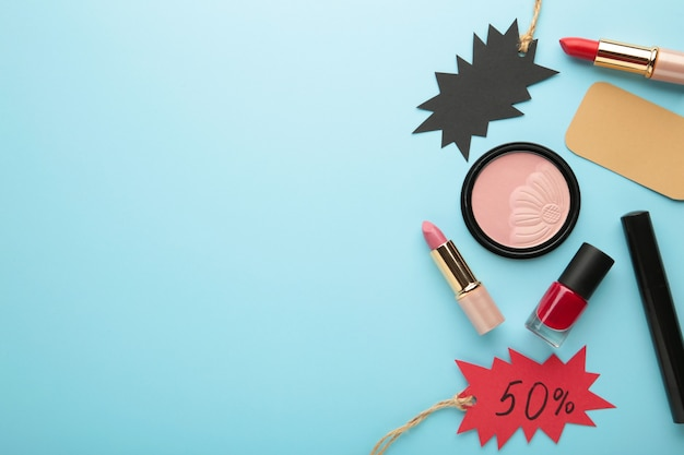 Set of cosmetics for sale on black friday on blue background. top view