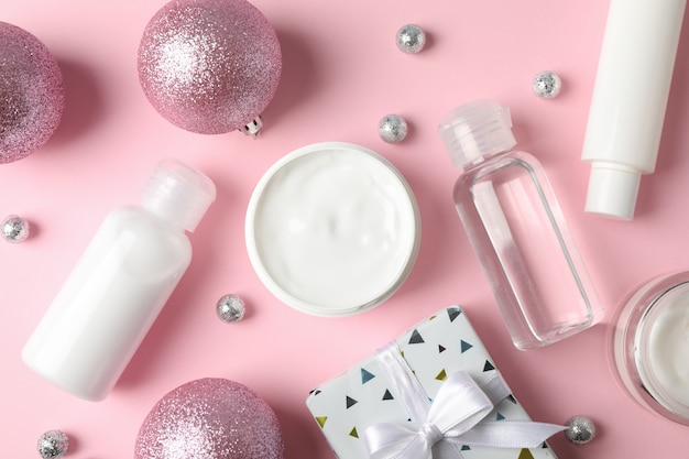 Set cosmetics, winter cream for skin, gift box on pink background, closeup. top view