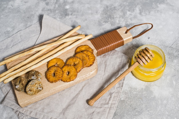 Set of crackers on wooden chopping board, honey.