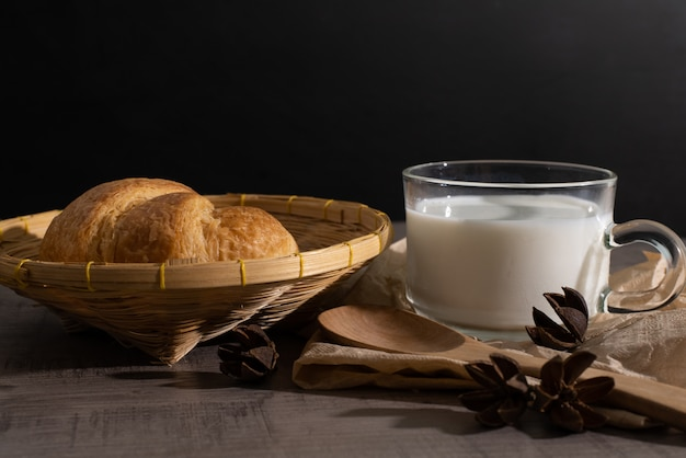 A set of croissant and cup of milk on the wooden table