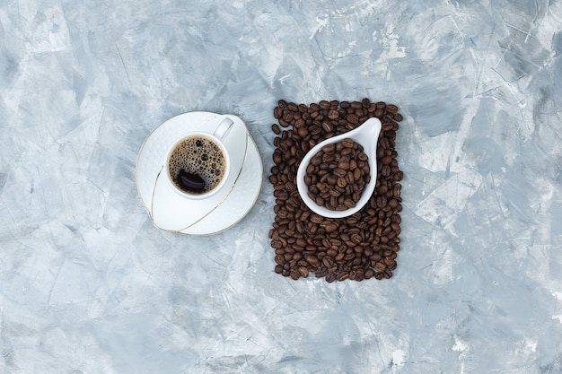 Set of cup of coffee and coffee beans in a white porcelain jug on a blue marble background. top view.