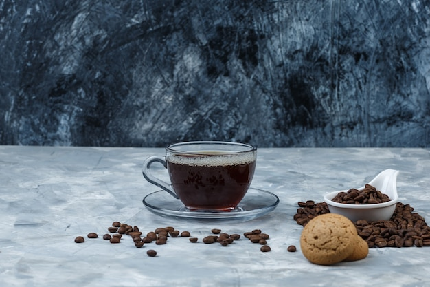 Set of cup of coffee, cookies and coffee beans in a white porcelain jug