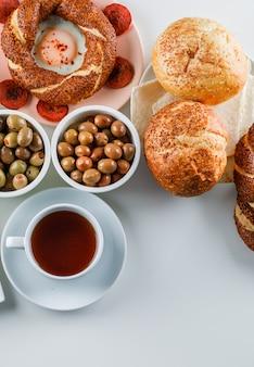 Set di una tazza di tè, bagel turco, olive, pane e uova con salsiccia in un piatto su una superficie bianca