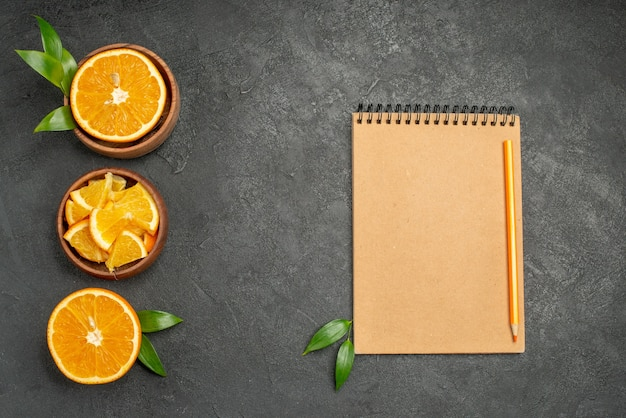 Set of cut in half sliced on pieces fresh orange leaves and notebook on black table