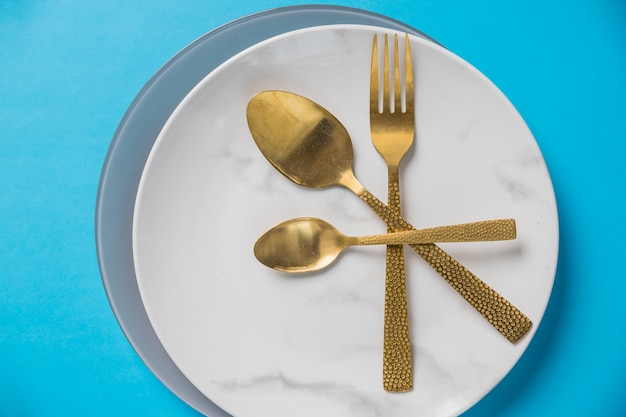 Set of cutlery spoon, fork, plate on blue wall. white marble plate. top view .table setting with gold silverware . styled elegant eating place setting