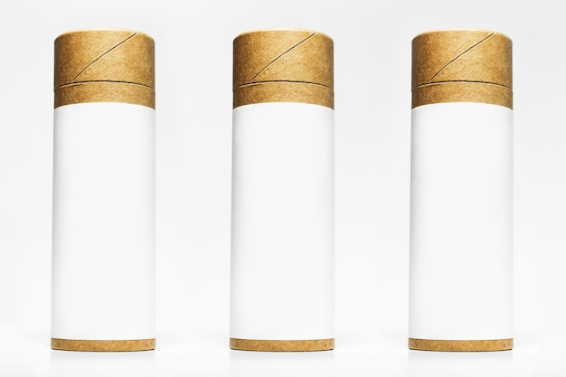 Set of cylinder cardboard boxes with empty sticker for mockup isolated on white studio surface