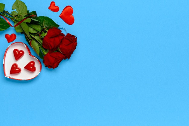 Set for a date. chocolates in a gift box, bouquet of roses, red soft hearts on a blue isolated.