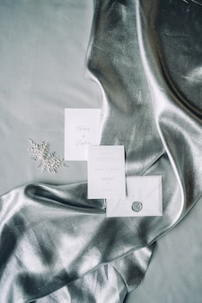 Set of decoration and wedding invitation on a cloth with gray textured background. top view.