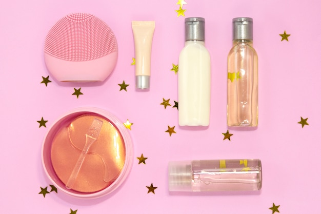 Set of decorative beauty accessories for woman, cream jars, gel bottles, silicone facial brush, hydrogel cosmetic eye patch on pink . flat lay, top view