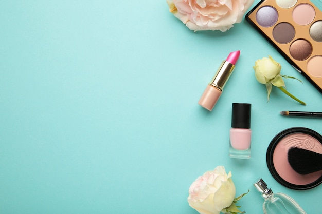 Set of decorative cosmetics with flowers on blue background. top view