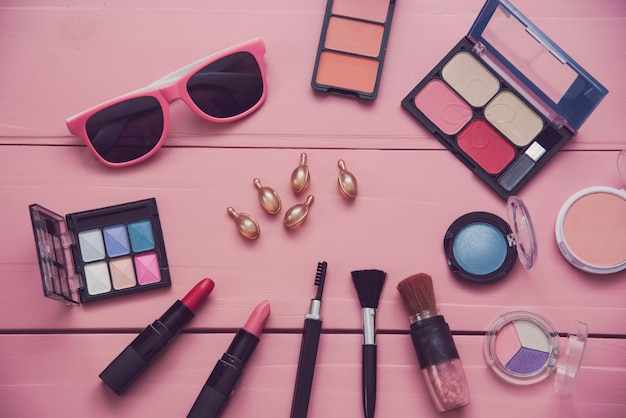 Set of decorative cosmetics for women on pink wood background