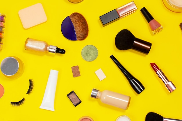Set of decorative cosmetics on yellow background. makeup cosmetics tools background