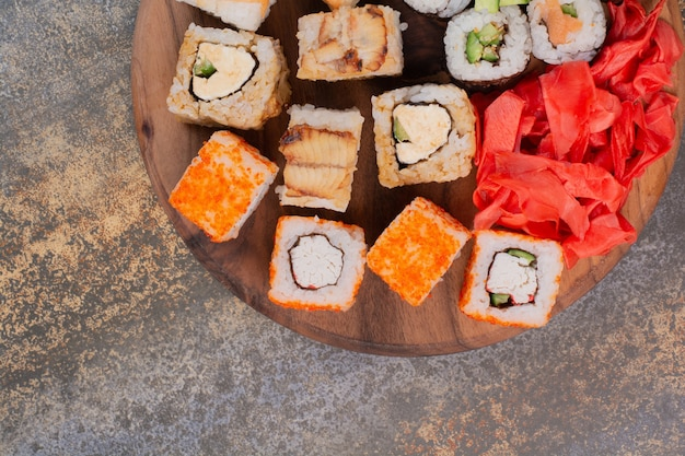 Set of delicious different sushi on wooden plate
