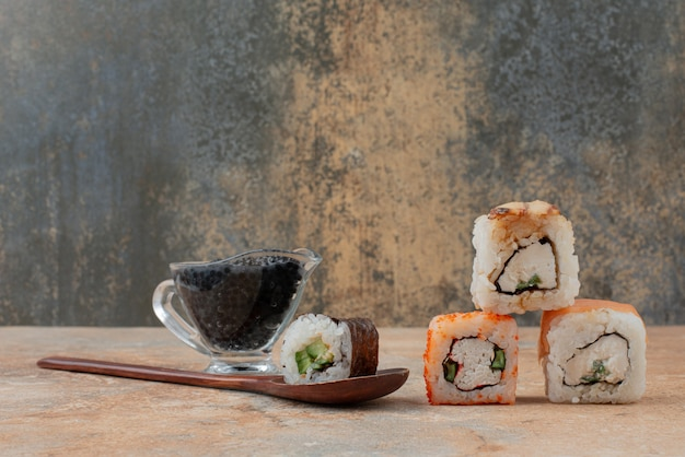 Set of delicious sushi roll with spoon and soy sauce on marble surface