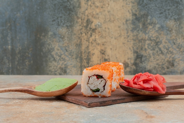 Set of delicious sushi roll with spoon and soy sauce on marble