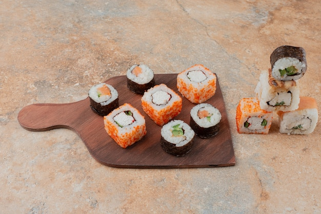 Set of delicious sushi on wooden plate