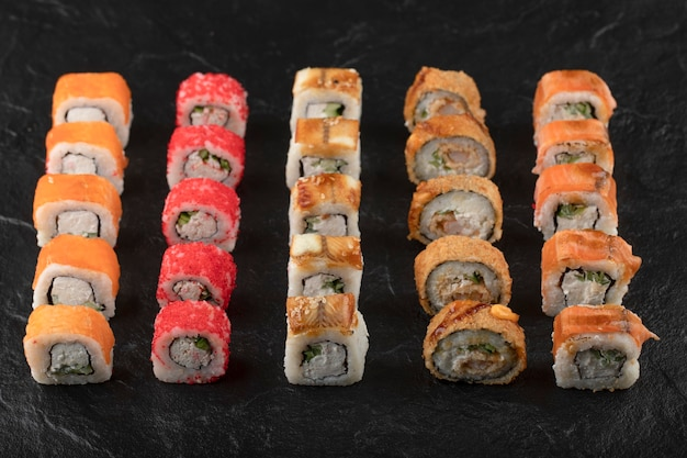 Set di deliziosi rotoli di sushi tradizionali su superficie nera