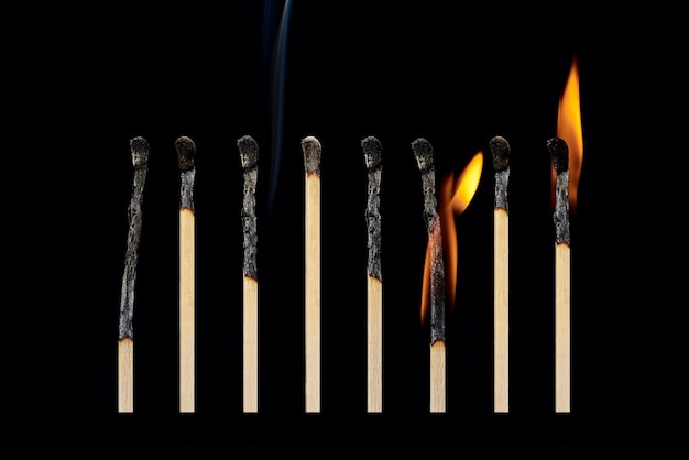 A set of different burnt matches with smoke with different fire isolated on a black background