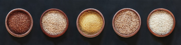 Set of different cereals and rice in wooden bowls on a black background, top view