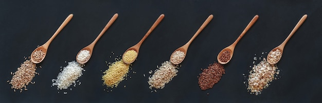 Set of different cereals and rice in wooden spoon ona  black background, top view