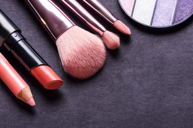 Set of different cosmetic brushed on black background