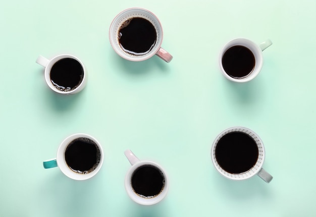 Set of different cups of coffee on mint background. top view, copy space, flat lay.