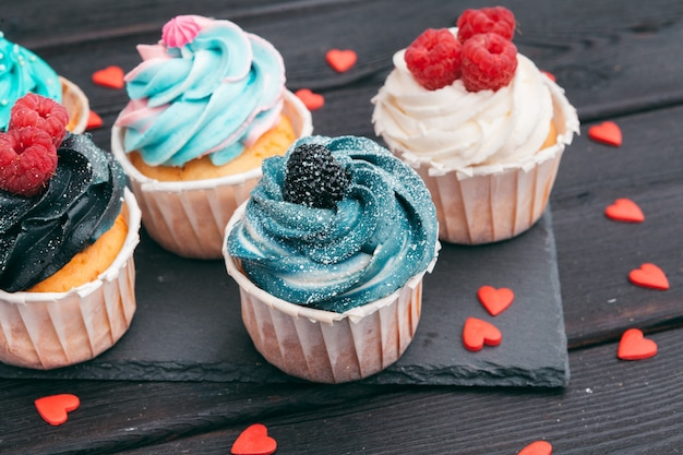 Set of different delicious cupcakes on dark