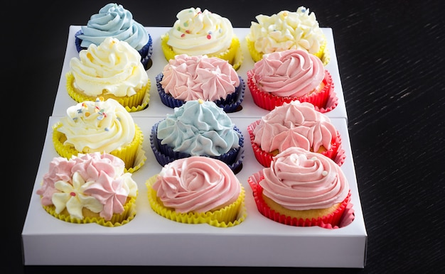 Set of different delicious homemade cupcakes in paper delivery box.