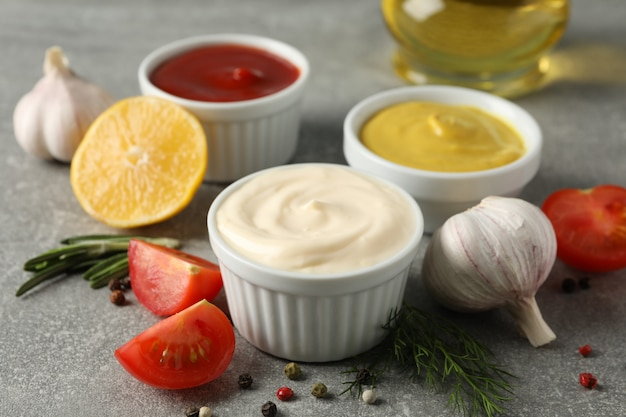 Set of different delicious sauces, garlic, cherry tomatoes, olive oil on gray background, closeup. space for text