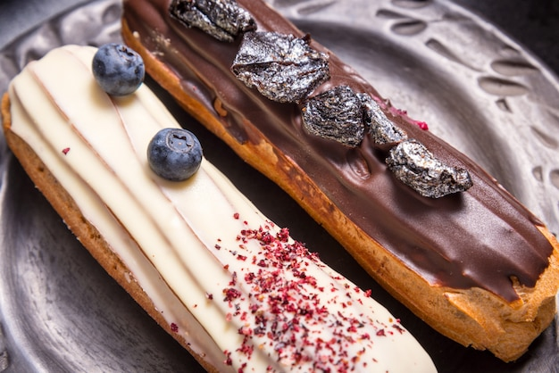 Set of different eclair cakes on dark backgrouns
