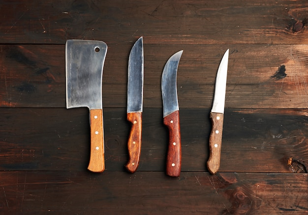 Set of different kitchen knives with wooden handles on a brown background from boards