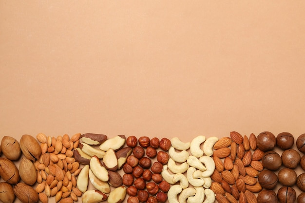 Set of different nuts on light beige background, space for text