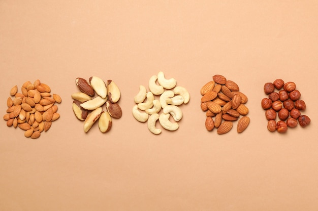 Set of different nuts on light beige background, top view