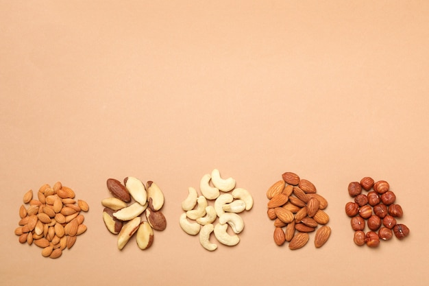 Set of different nuts on light beige wall, space for text