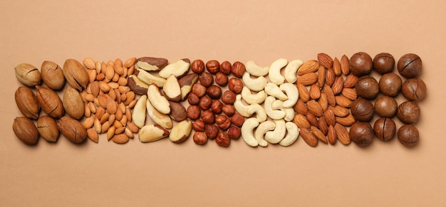 Set of different nuts on light beige wall, top view