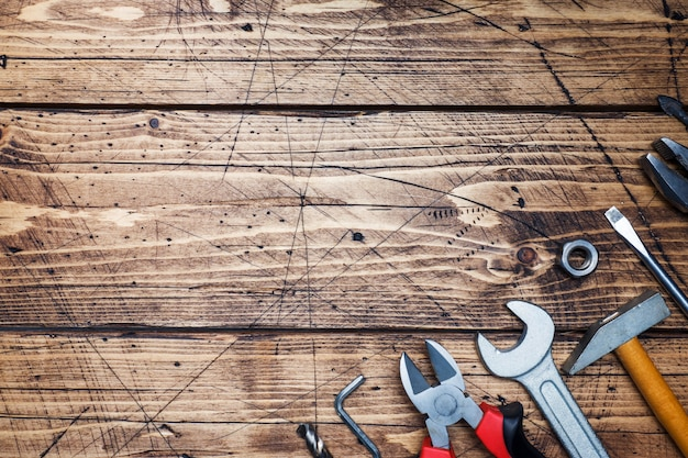 Set of different repair tools on wooden background with copy space.