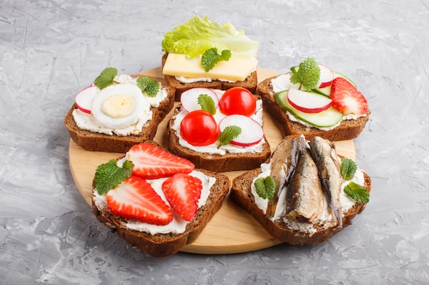 Set of different sandwiches with cheese, radish, lettuce, strawberry, sprats, tomatoes and cucumber on wooden board on a gray concrete. side view.